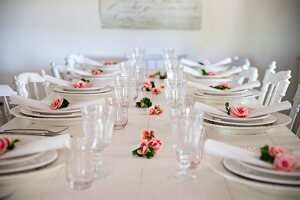 White place settings with roses and linen napkins on white wooden table