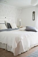 Double bed with white bedspread and grey and white pillows and scatter cushions in simple bedroom