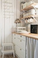 Detail of kitchen counter with wooden shelves of crockery and recipe written on white wooden wall