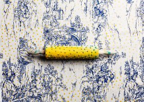 Printing yellow polka-dots on toile de jouy tablecloth using a modified rolling pin
