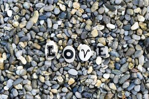 Letters on pebbles spelling out 'Love' on gravel surface