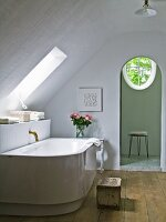 Philippe Starck bathtub with antique bronze tap fitting in purist bathroom