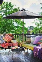 Sitzbänke mit Kissen und Sonnenschirm auf Terrasse in orientalischem Stil