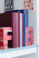 Colourful alphabet bookends on white bookshelf