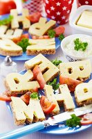 Buffet of bread and cheese cut into alphabet shapes on plates