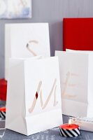 Paper-bag tealight lanterns with cut-out letters