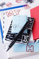 Various notebooks and letter-shaped paperclips