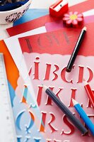 Plastic letter stencil and pens on sheets of coloured paper