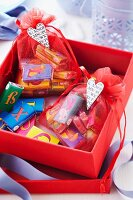 Chocolate bars with alphabet wrappers in small organza bags in red gift box
