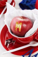 Apple with letter cut-out in red cup