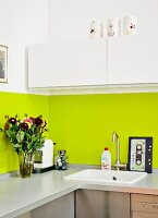 Kitchen counter with lime green splashback, white wall units, bouquet, coffee machine and cassette-tape chopping board