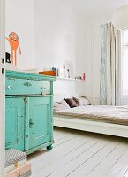 Shabby-chic bedroom with turquoise baby-changing cabinet, white-painted wooden floor and curtains made from bed linen
