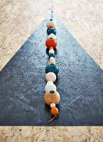 Black triangle and string of colourful wooden beads with candleholders on chipboard dining table