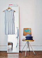 Stack of hats on painted, Danish, architect-designed chair next to dress on coat hanger hung on mirror