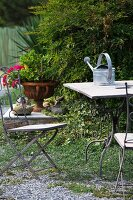Garden table with watering can and garden chair in front of bush and planted urn