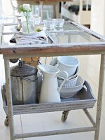 Various kitchen utensils and crockery on serving trolley in kitchen