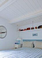 Doppelbett mit karierter Bettwäsche in rustikalem Schlafzimmer mit weiss gestrichener Holzdecke