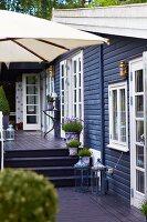 Split-Level-Terrasse vor Holzhaus mit weissen Sprossenfenstern