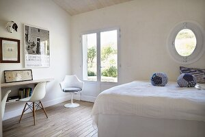 White bedroom with fabric spheres on bed and classic chairs to one side in front of French windows