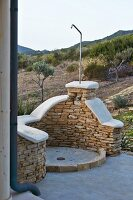 Outdoor shower with half-height stone wall in front of Mediterranean landscape