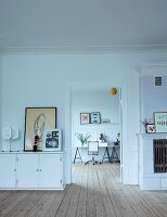 White sideboard next to open door with view of office area; continuous wooden board floor