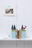 Hand-crafted bookends with winter motifs decorated with miniature deer and tiny fir trees on shelf on white, wooden wall