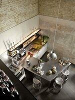 View down into kitchen area with stainless steel counter and bar stools in corner of rustic, loft-apartment interior with half-exposed brick walls