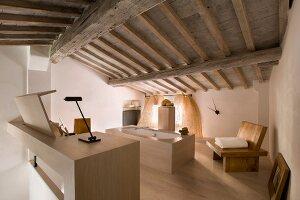 Offenes Bad mit freistehender Designer Badewanne, seitlich massiver Holzstuhl, in renoviertem Dachgeschoss mit rustikaler Holzbalkendecke