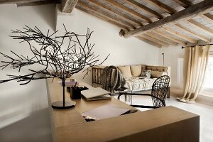 Kunstobjekt auf Schreibtisch in renoviertem, rustikalem Dachgeschoss mit Holzbalkendecke und elegantem Flair
