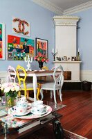 Dining area with antique chairs painted different colours and bright artworks on wall in period apartment; glass table on castors in foreground