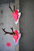 Two hunting trophies painted neon pink hanging on concrete wall