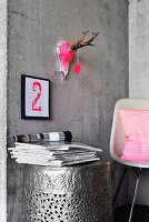 Hunting trophy painted neon pink above printed number on concrete wall above barrel-shaped table made from hammered metal