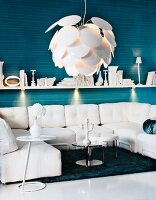 Seating area with white furnishings - designer pendant lamp with overlapping, fish-scale lampshade above sofa combination below wall-mounted shelf with spotlights on blue striped wall