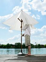 A young man opening a patio parasol on a jetty