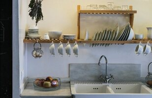 Crockery on wooden draining rack above sink