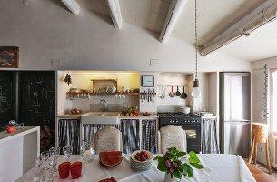 Esstisch mit weisser Tischdecke gegenüber Küchenzeile in rustikalem Esszimmer mit Holzbalkendecke