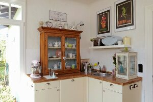Kitchen with small, glass-fronted cabinet on wooden worksurface and base units with cream doors