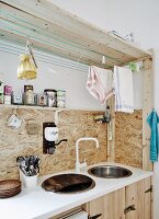 Kitchen counter made from simple wooden elements from DIY store with old linen tea towels hanging from washing lines