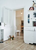 View past vintage, white-painted kitchen dresser into spacious foyer of period apartment