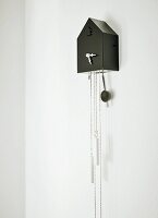 Modern, black cuckoo clock with retro-style hands