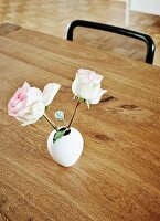 Two roses in small, white retro vase on wooden table