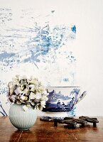White, spherical vase of hydrangeas and white and blue painted bowl (toile de jouy) against wall with blue plant-like structure on white background