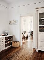 Traditional country-house kitchen with white-painted cupboards, view into dining room through open door and continuous wooden flooring