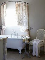White chair and side table next to vintage bathtub below shower curtain on semi-circular curtain rail