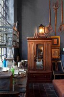Antique wooden wardrobe in corner below wooden pitchforks hung on black-painted wall
