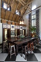 Long, dark wood counter and various barstools on chequered floor in kitchen with view of exposed, rustic roof structure