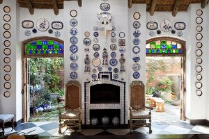 Antique chairs flanking fireplace below decorative plates hung on walls; open terrace doors with view of sunny courtyard on either side