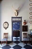 Antique chairs with blue and white seat cushions flanking open door with view of kitchen counter and blue-tiled wall in vintage interior