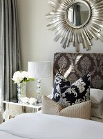 Scatter cushions on bed against upholstered headboard with ornate pattern below mirror with sunburst frame