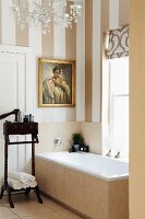 Antique, dark wood valet stand next to bathtub below window in bathroom with striped wallpaper